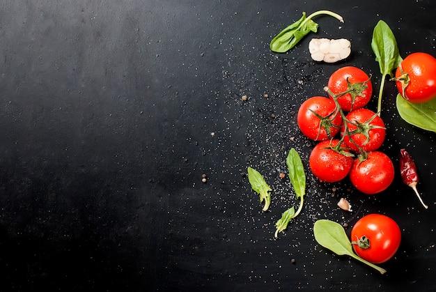 Ripiano del tavolo rustico nero con ramo di pomodori ed erbe aromatiche, vista dall'alto