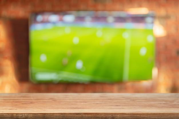 Ripiano del tavolo vuoto sul fondo del muro di mattoni con la tv
