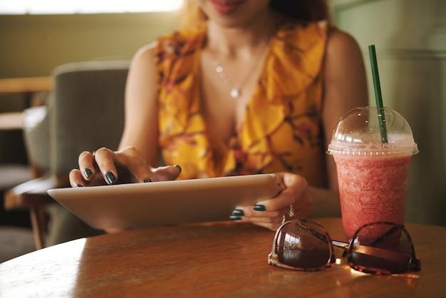 Riposando nella caffetteria con tavoletta digitale