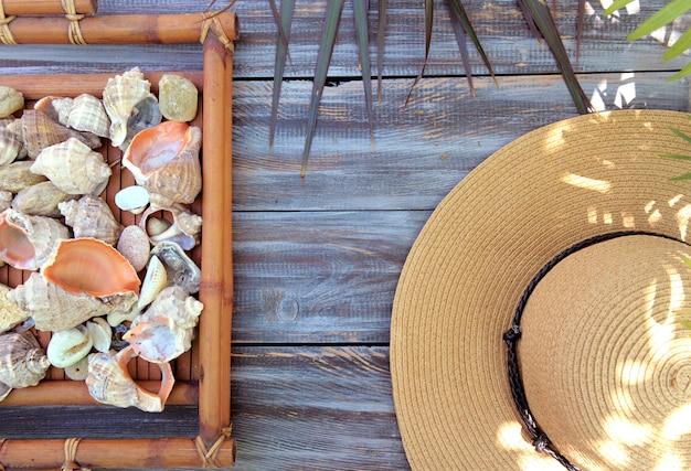 Riposo estivo mock up con cappello e conchiglie su un tavolo di legno