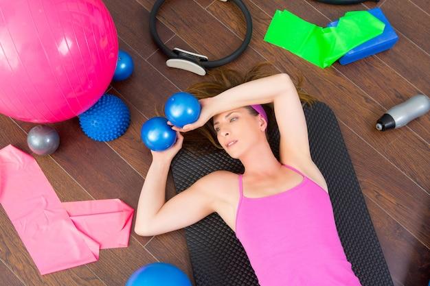 Riposo stanco della donna di aerobica che si trova sulla stuoia