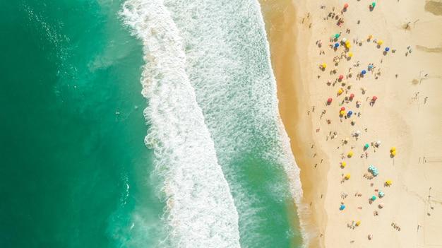 Ripresa aerea bloccata delle onde che si infrangono sulla riva. ombrelloni colorati e persone che si godono l'estate.