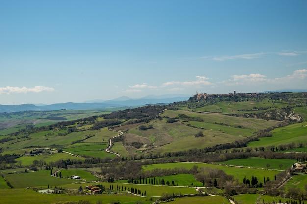 Ripresa aerea dei campi ricoperti di erba mozzafiato sotto il bel cielo catturato in italia