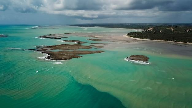 Ripresa aerea dell'oceano turchese brasiliano con un cielo nuvoloso