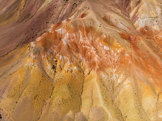 Ripresa aerea delle montagne gialle e rosse strutturate che ricordano la superficie di marte