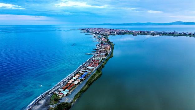 Ripresa aerea di case sulla riva stretta in mezzo al mare