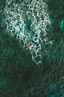 Ripresa aerea di surfisti che fanno surf al momento del tramonto. foto fornita con drone. concetto di natura e sport