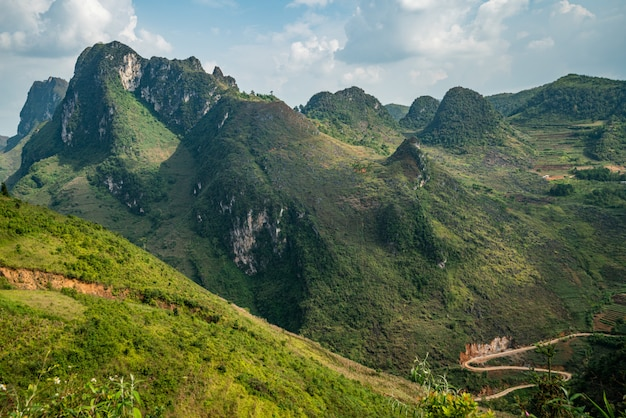 Ripresa aerea di un bellissimo paesaggio verde con alte montagne sotto il cielo nuvoloso