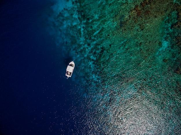 Ripresa aerea di una barca sul bellissimo oceano blu nel bonaire, caraibi