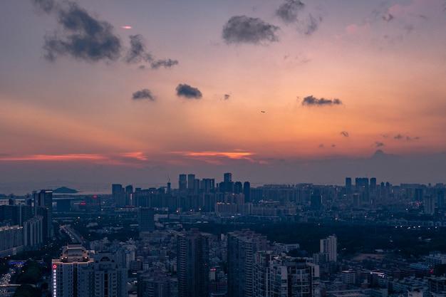 Ripresa aerea di una grande città sotto un cielo nuvoloso blu-arancio al tramonto