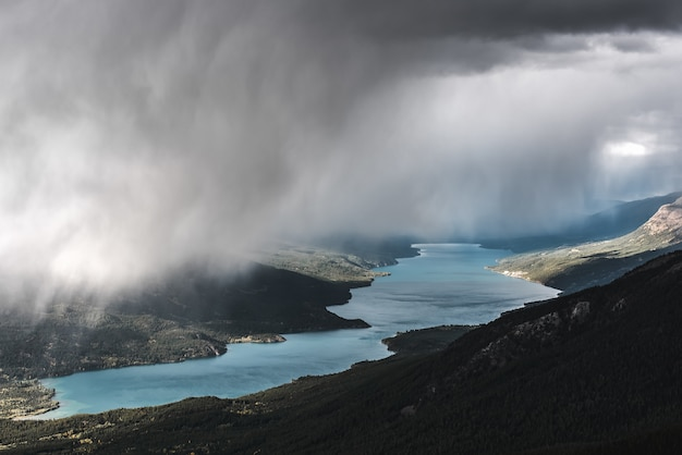 Ripresa aerea di una montagna boscosa vicino a un fiume sotto un cielo nebbioso