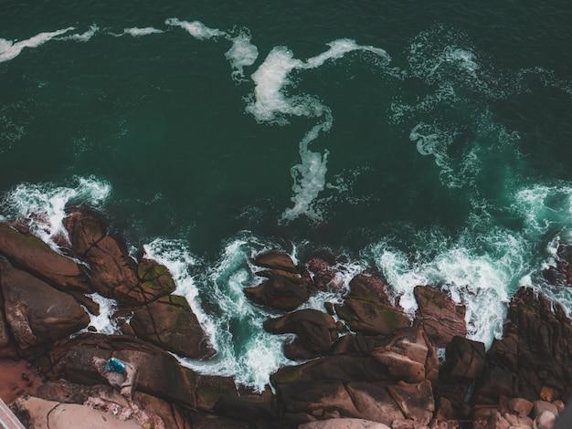 Ripresa aerea di una spiaggia rocciosa e del mare con spruzzi d'acqua