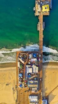 Ripresa aerea verticale di un parco con diversi tipi di giostre in spiaggia