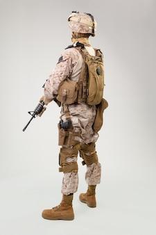 Ripresa in studio del moderno soldato di fanteria, fuciliere marino americano in uniforme da combattimento, elmo e armatura