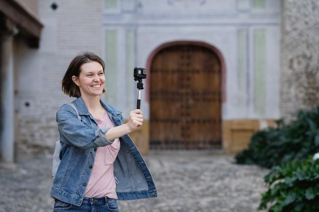 Riprese della ragazza del viaggiatore soddisfatte della macchina fotografica di azione. giovane donna attraente che cammina sulla strada godendo il suo tempo di vacanza.
