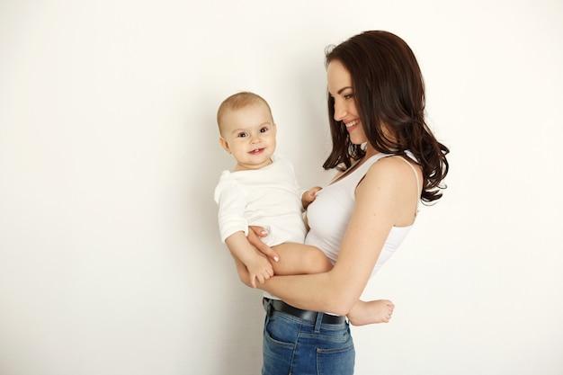 Risata sorridente della giovane bella madre felice che tiene sua figlia del bambino sopra la parete bianca.