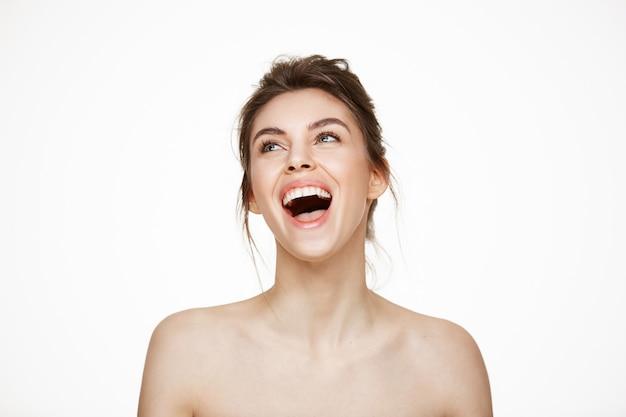 Risata sorridente di esultanza della bella ragazza nuda allegra sopra il fondo bianco. trattamento facciale. bellezza e salute.
