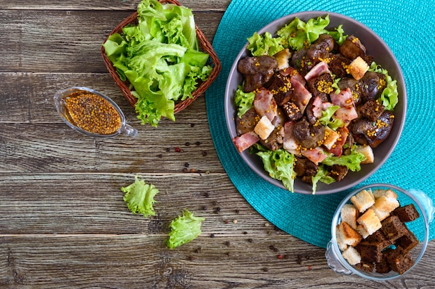 Riscalda in una ciotola l'insalata sana di fegato di pollo, crostini di segale, pancetta affumicata, insalata verde e salsa di senape