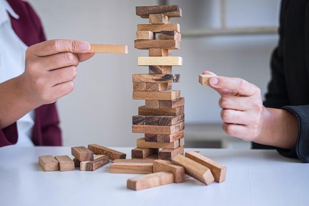 Rischio alternativo e strategia nel mondo degli affari, gioco d'azzardo cooperativo della squadra di affari che mette la gerarchia dei blocchi di legno sulla torre alla pianificazione collaborativa e allo sviluppo per il successo