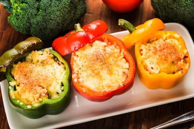Riso ai frutti di mare con formaggio, peperoni ripieni con riso e carne macinata. peperone verde grigliato con formaggio