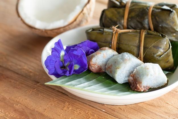 Riso appiccicoso del dessert tradizionale tailandese con le banane (khao tom mat) su fondo di legno