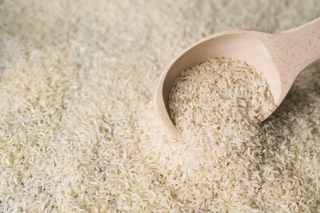 Riso bianco in un cucchiaio di legno sul fondale