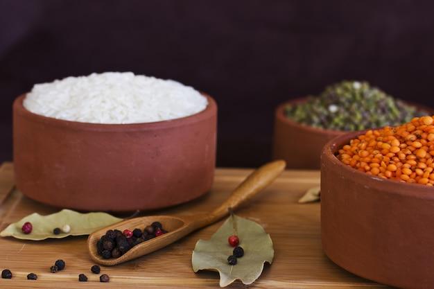 Riso bianco, lenticchie rosse e piselli mache sul vassoio in legno. baia