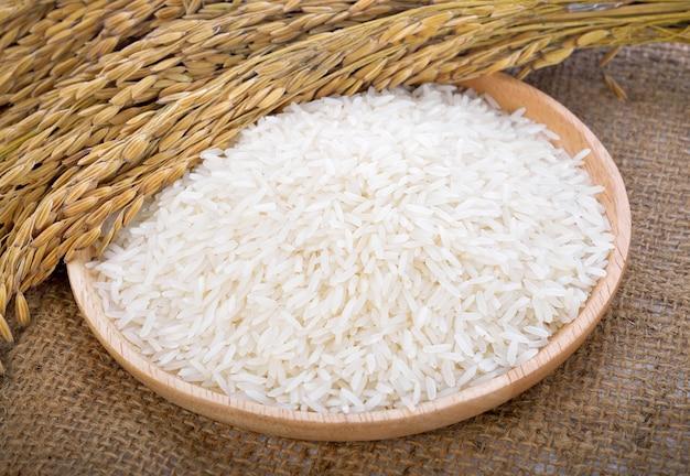 Riso bianco sulla piastra in legno e pianta di riso