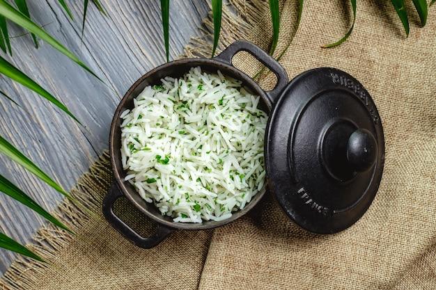 Riso bollito con erbe in una padella su un tavolo di legno