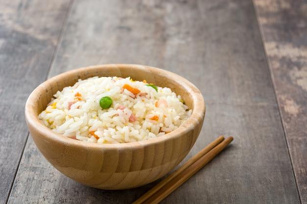 Riso cinese fritto con le verdure sullo spazio di legno della copia della tavola