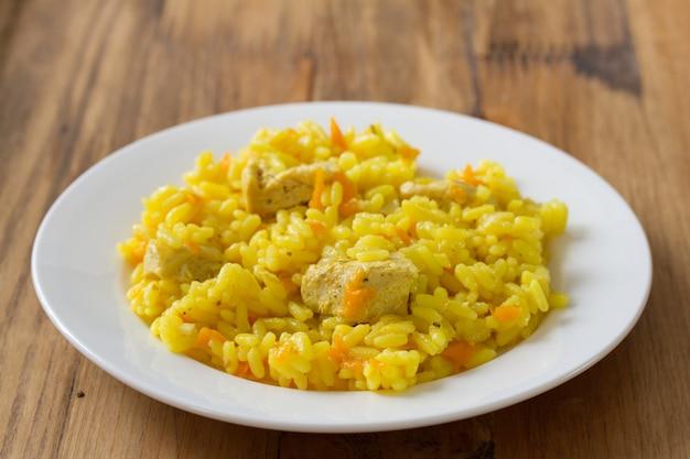 Riso con carne e la carota sul piatto bianco