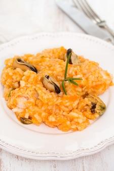 Riso con frutti di mare sul piatto bianco