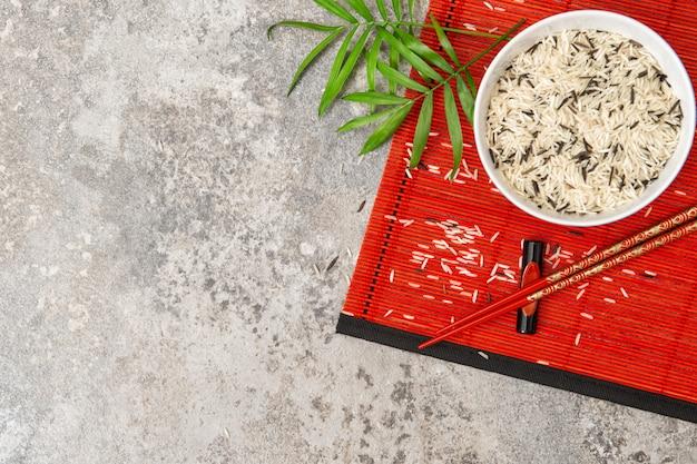 Riso con le bacchette bambù rosso sfondo opaco