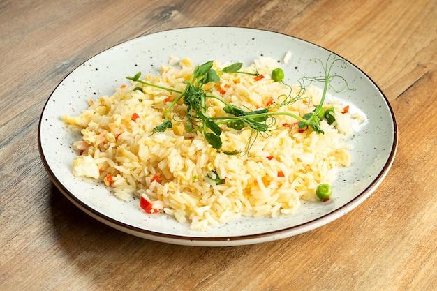 Riso con le verdure e l'omelette in piatto del whte su fondo di legno. alimento sano ed equilibrato per atleti e dieta.