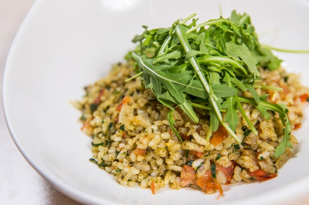 Riso con le verdure e la rucola in piatto bianco sulla tavola di legno leggera in un ristorante