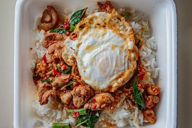 Riso condito con pollo fritto al basilico e uovo fritto.