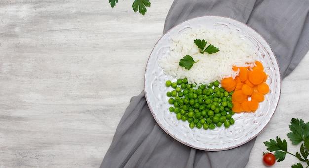 Riso cotto con verdure e prezzemolo sul piatto su stoffa grigia