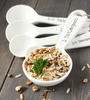Riso crudo del multigrain in porcellana che misura i cucchiai su fondo di legno