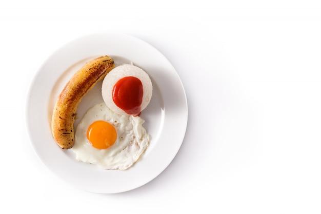 Riso cubano tipico con la banana fritta e l'uovo fritto su un piatto isolato su bianco
