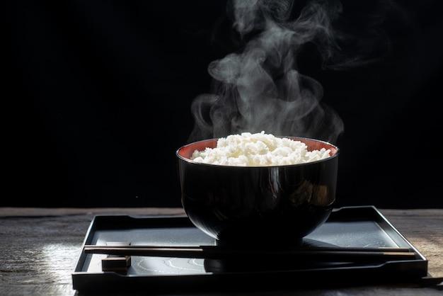 Riso cucinato con vapore in ciotola nera su fondo scuro, riso cucinato caldo nel fuoco selettivo della ciotola, alimento caldo e sano