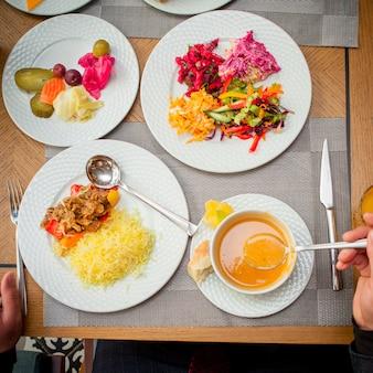 Riso della minestra mangiatrice di uomini di vista superiore con insalata della verdura e della carne sulla tavola