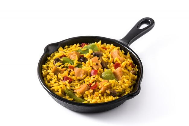 Riso fritto con il pollo e le verdure sulla padella del ferro da stiro isolata