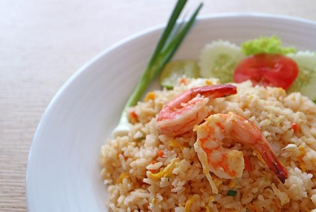 Riso fritto di stile tailandese con gamberetti o khao pad goong su un piatto bianco