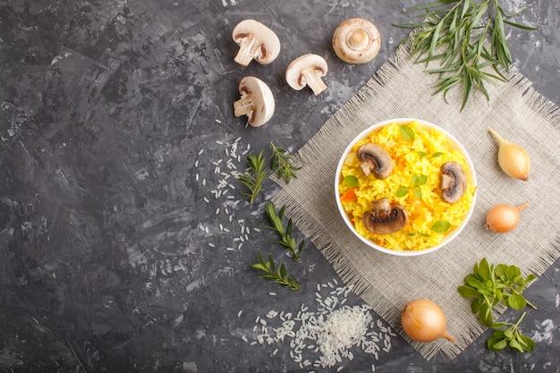 Riso fritto giallo con funghi champignon, curcuma e origano in ciotola in ceramica bianca su uno sfondo di cemento nero