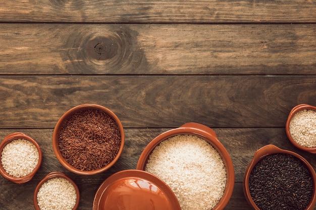 Riso integrale marrone al gelsomino; riso bianco e riso biologico in una ciotola sul tavolo di legno