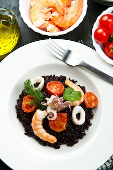 Riso nero con calamari a fette, gamberi e pomodoro sul piatto bianco