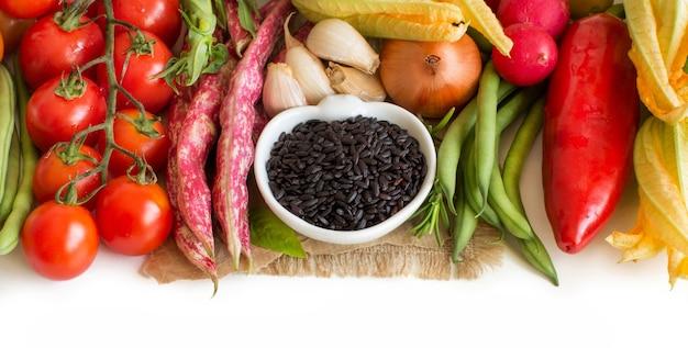 Riso nero selvatico in una ciotola con verdure isolate sulla fine bianca su