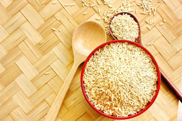Riso organico sul pavimento di bambù rishi il riso in ciotola o in cucchiaio sul pavimento di bambù .topview, spazio della copia.