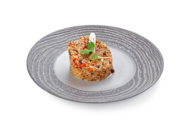 Riso preparato con verdure sul piatto isolato su bianco