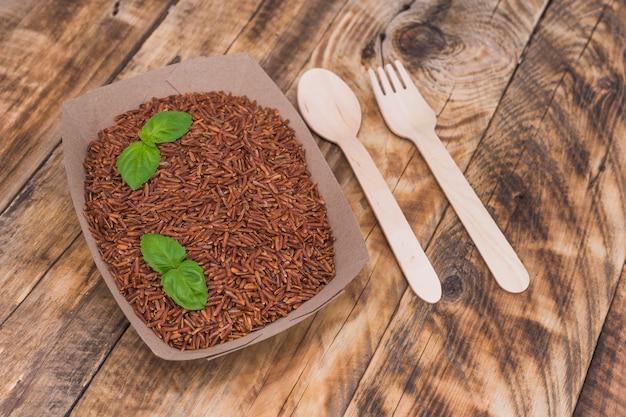 Riso rosso crudo in contenitore con foglie di basilico; cucchiaio e forchetta sulla superficie in legno